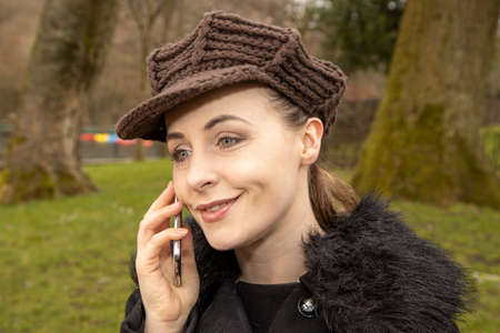 An attractive young woman in a public park on a cold day in the winter time on the phone looking inquisitive while she is thinking