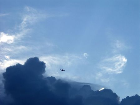 lightbeam: commercial airplane coming out of the clouds Stock Photo