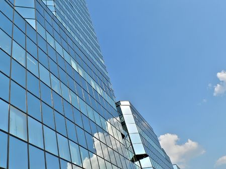 blue building in warsaw with clouds reflection