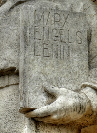engel: Closeup of a statue outside the palace of culture in warsaw with a cover book where Stalin name was removed