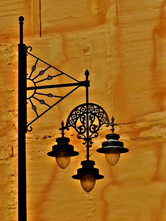 Old lamp post over orange background in Cartagena Spain Stock Photo - 1457033
