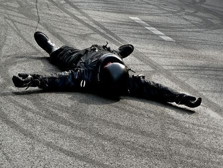 biker on the road after an accident (stunt) Stock Photo