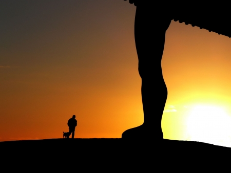 Silhouette of man with his dog passing by the Angel of the North sculpture at sunset photo