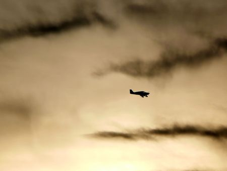 airborne vehicle: Silhouette a a small plane fly at dusk Stock Photo