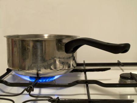 Saucepan on stove with gas stove lit on