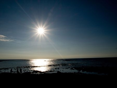 reflecting: Group of three people at the beach  against bright sunshine reflecting in the ocean Stock Photo