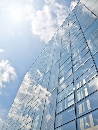 Blue offices building with clouds reflection under the sun