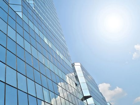 Blue offices building with clouds reflection under the sun photo