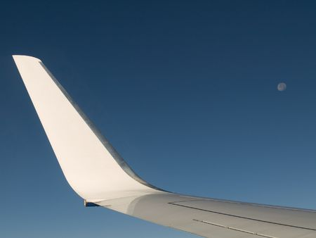 Airliner wing with blue sky and moon photo