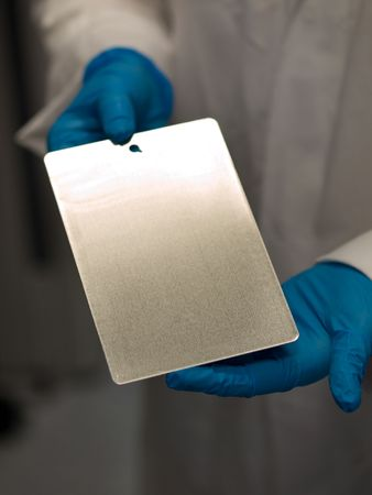 Scientist at work holding a test coating plate