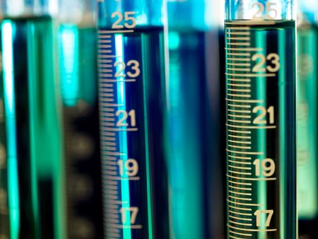 Graduated cylinders in a laboratory  filled with blue dye