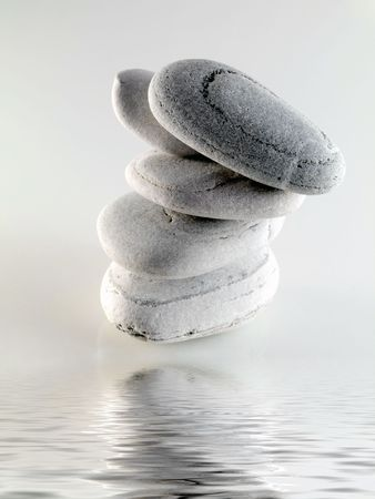 white off beach stones with water reflection