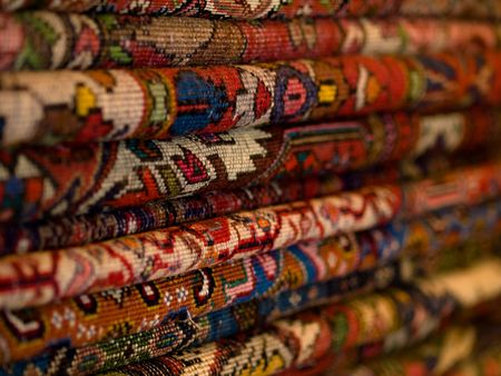 Closeup of a stack of colorful persian carpets with shallow depth of field