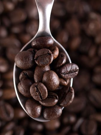 Spoon fillled with coffee beans with selective focusing