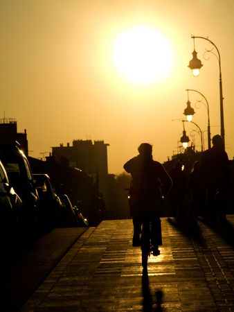 Cyclist on the sidewalk of the Pont Neuf bridge  at sunset in the city of toulouse