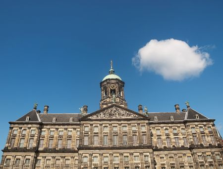 Royal palace of Amsterdam at the Dam square under blue sky with single fluffy cloud