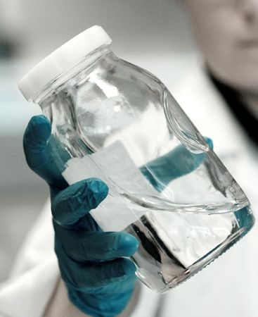Chemist wearing blue latex gloves holding a flask full of liquid polymers in a research lab Stock Photo
