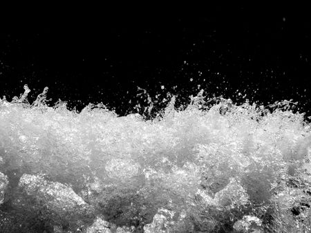 Powerful stormy river with water drops captured on black background