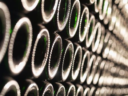 Row of Bordeaux wine bottles stacked in a cellar with shallow depth of field Stock Photo - 5988175