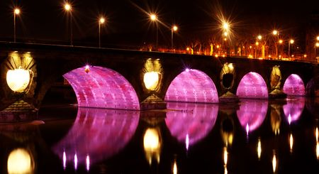 Pont neuf bridge illuminated at night with pink lights over the garonne in the city of Toulouse in France Stock Photo