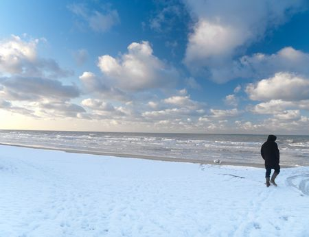 Man walking in snowy beach along the North sea in France