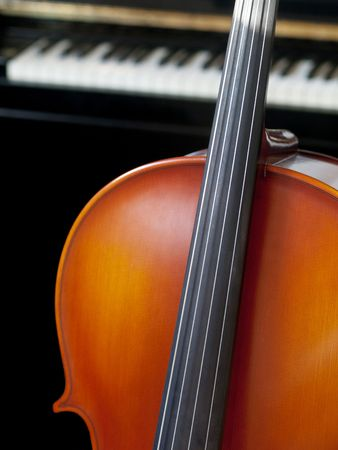 Cello standing in front on a piano photo