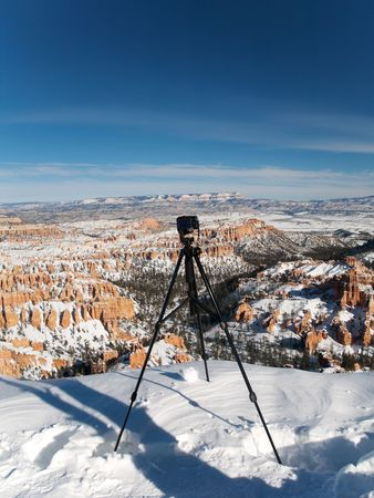 Camera on tripod standing on the rim of Bryce Canyon during winter photo