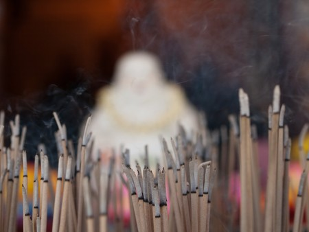 Burning incense sticks in a Chinese temple in Malaysia with blurry Buddha in the background