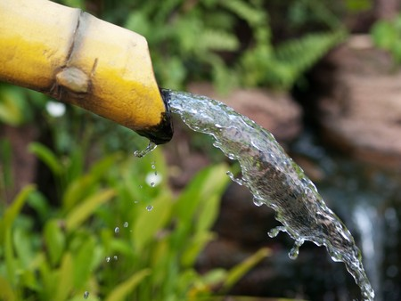 Pure water coming out from a yellow bamboo shot  in a Chinese garden Stock Photo