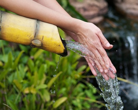 Asian woman cleaning her hands in a pure water stream
