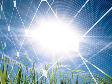 Beautiful grass field at spring against the sun with photovoltaic panel