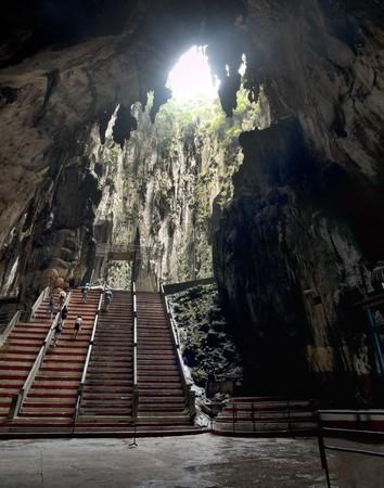 Inside Batu caves in Kuala Lumpur Malaysia with people climbing stairs