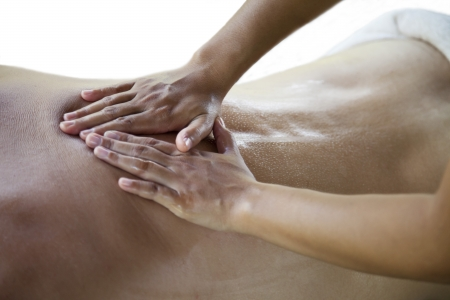 Therapist  giving a back massage at a young male in a spa Stock Photo