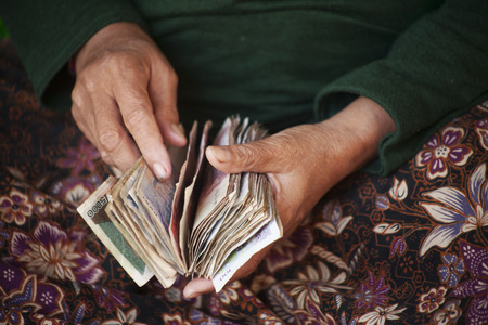 Ederly woman  counting riel notes in a market in Cambodia