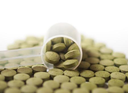 oleifera: Close up of Moringa  oleifera tablets with measuring plastic spoon on pure white background