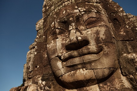 khmer: Beautiful faces carved in sandstone at Bayon temple in Siem Reap Cambodia