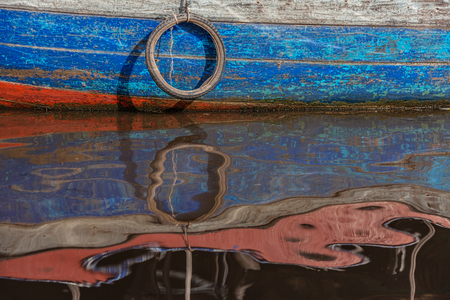 water transportation: Nice boat colored red and blue eflection with a tire Stock Photo