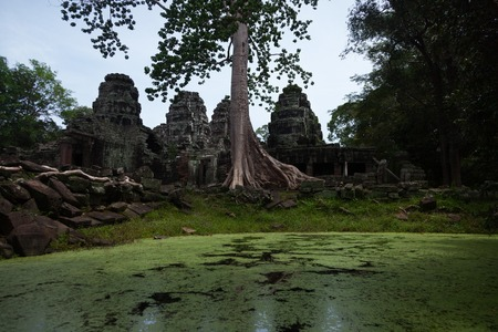 Bnatey Kdei temple in Angkor with green pond filled with water