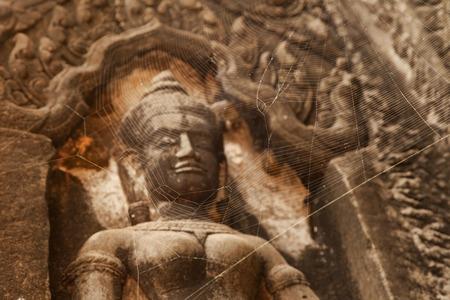 phrom: Devata statue in Ta Phrom temple with spider web