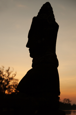 Giant statue silhouette at sunset Angkor Thom