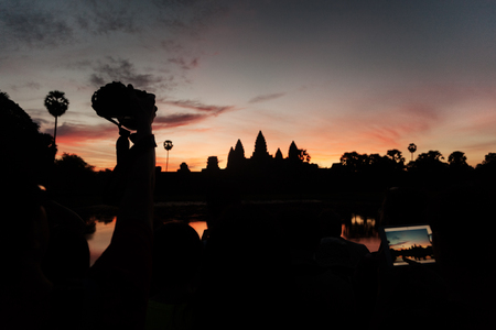 Tourist taking pictures at Angkor Wat temple at sunrise