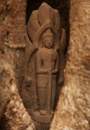 Small hidden sandstone statue in Angkor temple inside a tree Stock Photo