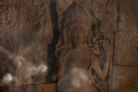 Devata carving with fumes in Preah Khan temple Stock Photo