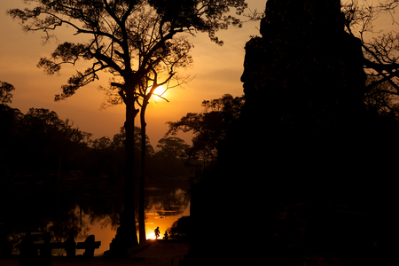 Beautiful sunset at a gate of Angkor Thom with moat