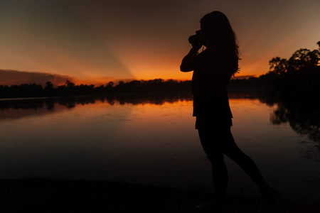 Silhouette of a female photographer at sunset Stock Photo
