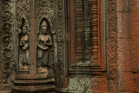 Devatas carving in Ta Prohm temple with red walls Stock Photo