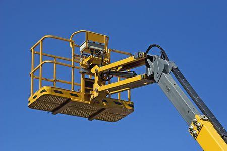 Yellow construction crane basket against blue sky.
