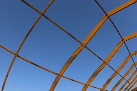 Unfinished wooden roof construction over the blue sky. Stock Photo