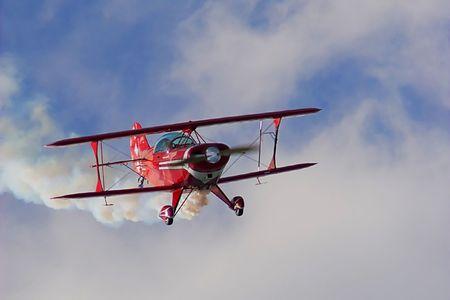 空気で、古い赤い複葉機を示しています。 写真素材