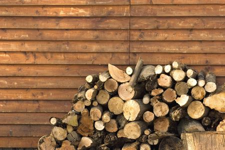 dry  pile of logs stacked near house wall. Standard-Bild